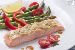 Rosemary Roasted Salmon. Served with asparagus, cherry tomatoes, red bell pepper topped by mustard rosemary sauce and slice of lemon for healthy style dinner stock photography