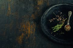 Rosemary and seasoning in bowl on rustic timber Royalty Free Stock Photography