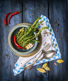 Rosemary and spaces in blue bowl on napkin with fork and spoon, blue wooden background. Top view Stock Photography