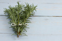 Rosemary sprigs. A bunch of rosemary sprigs tied together on a blue wooden board Stock Photo