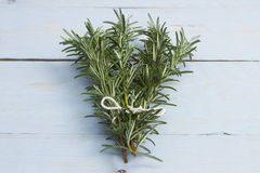 Rosemary sprigs. A bunch of rosemary sprigs tied together on a blue wooden board Royalty Free Stock Photo