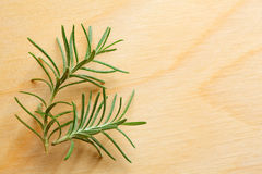 Rosemary twig on chopping board Royalty Free Stock Photography