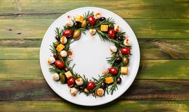 Rosemary wreath christmas appetizer with cheese and olives stock image