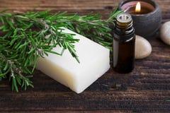 Rosemary zeep en etherische olie aromatherapy met kaars op hout stock foto