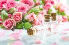 Rosen-ätherisches Öl und Rosenblumen auf weißem Holztisch stockfotografie
