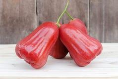 Rosen-Apfel reichte einen Holztisch ein Stockfoto