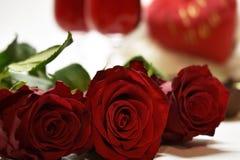 Rosen auf den Hintergrundgläsern mit Wein Stockbild
