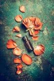 Rosen blüht mit dem Blumenblatt und ätherischem Öl auf rustikalem Weinlesehintergrund, Draufsichtverfassen Lizenzfreie Stockfotos