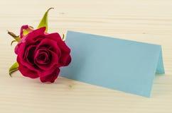 Rosen-Blume mit leerer Einladungskarte auf hölzernem Hintergrund Stockfotos