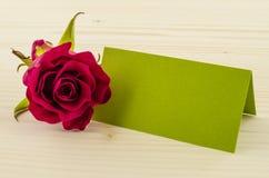 Rosen-Blume mit leerer Einladungskarte auf hölzernem Hintergrund Stockfoto