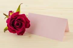 Rosen-Blume mit leerer Einladungskarte auf hölzernem Hintergrund Lizenzfreies Stockbild