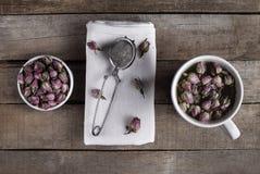 Rosen-Blume mit Tee und Sieb Stockfotografie