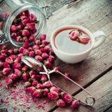 Rosen-Blumen, Teeschale, Sieb und Glasgefäß mit den rosafarbenen Knospen Stockbild