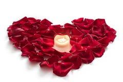 Rosen-Blumenblätter in der Herzform mit Kerze lizenzfreie stockbilder
