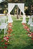 Rosen-Blumenblätter, die auf das grüne Gras auf der Hochzeitszeremonie legen lizenzfreies stockfoto