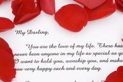 Rosen-Blumenblätter und ein Liebesbrief. Stockfoto