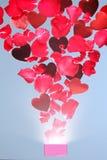 Rosen-Blumenblätter und -herzen, die aus einer Geschenkbox heraus fliegen Lizenzfreie Stockfotos
