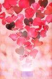 Rosen-Blumenblätter und -herzen, die aus einer Geschenkbox heraus fliegen Lizenzfreie Stockbilder