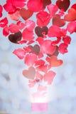 Rosen-Blumenblätter und -herzen, die aus einer Geschenkbox heraus fliegen Stockfotos