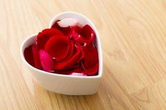 Rosen-Blumenblattblume in der Herzschüssel stockbild