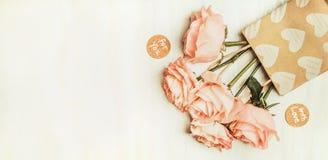 Rosen in der Einkaufstasche mit Liebe Mitteilungs-Zeichen und im Herzen auf hellem Hintergrund, Draufsicht Lizenzfreies Stockfoto