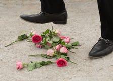 Rosen, die an von einer Person gebrochenen Herzens gestampft werden Lizenzfreie Stockfotografie