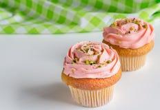 Rosen för två rosa färger virvlade runt frostade koppkakor med sprin för pistaschmutter Royaltyfri Bild
