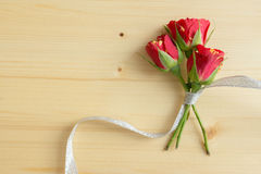 Rosen gebunden mit Band auf einer Holzoberfläche Stockfotos