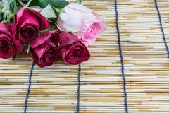 Rosen gesetzt auf Vorhänge 2 eines gesponnene Holzes Stockfotos