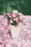 Rosen im weißen Vase auf einem Holztisch Stockfotografie