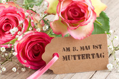 Rosen mit Papiertag auf verwittertem Holz Stockbilder