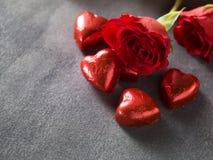 Rosen mit Schokoladenherzen auf einem Hochzeitstageshintergrund Lizenzfreie Stockfotografie