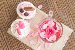 Rosen-Tee und Bonbonkleiner kuchen auf Tabelle Lizenzfreies Stockfoto