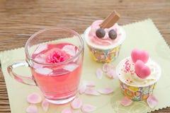 Rosen-Tee und Bonbonkleiner kuchen auf Tabelle im Garten Lizenzfreie Stockbilder