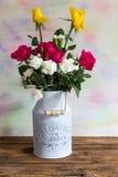 Rosen und Gartennelken im Milchkanister Stockfoto