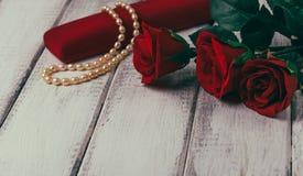 Rosen und Geschenkbox mit Perle auf Holztisch Roter heart-shaped Schmucksachegeschenkkasten und eine rote Spule auf einem Zeichen Lizenzfreies Stockbild