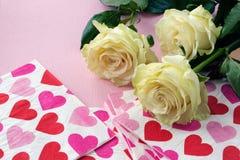 Rosen und Servietten mit roten Herzen stockbild