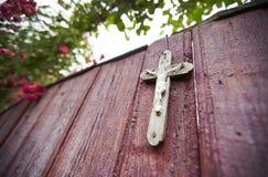 Rosenbusch auf hölzernem Tor mit einem Kreuz Stockfoto