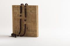 Rosenkranzperlen auf leerem Korkenbuch Stockfotografie