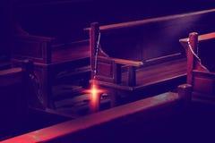 Rosenkranzperlen, die an den hölzernen Kirchenbänken hängen stockbild