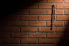 Rosenkranzperlen, die an der Backsteinmauer hängen Stockbild