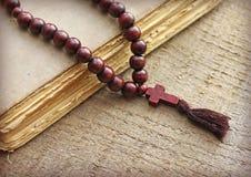 Rosenkranzperlen und heilige Bibel auf hölzernem Hintergrund Lizenzfreie Stockfotografie