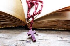 Rosenkranzperlen vom roten Holz mit Kreuz in einem alten Buch auf einem rusti lizenzfreie stockbilder