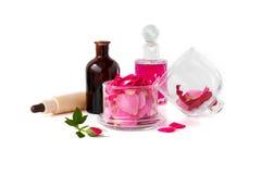 Rosenwasser und rosafarbenes Öl, Blumenblätter von Rosen-Damascene auf dem weißen Hintergrund lizenzfreies stockbild