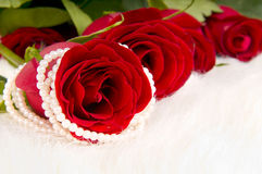Roses. Bouquet beautiful red roses and pearl necklace; lay on white to fur Stock Photo