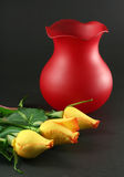 Roses. Three yellow roses with red vase on dark background Stock Photos