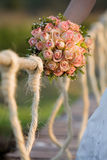 Roses. A vertical photo of a caucasian bride holding a rose bouquet on a rope bridge Royalty Free Stock Photo