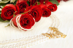 Roses. Bouquet beautiful red roses and pearl necklace; lay on white to fur Royalty Free Stock Photos