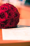 Roses and marrige certificate. Image showing a bouquet of red roses next to a romanian wedding certificate on a blurry background Royalty Free Stock Images