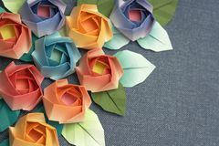 Roses. Origami roses decoration on a greyish blue background royalty free stock image
